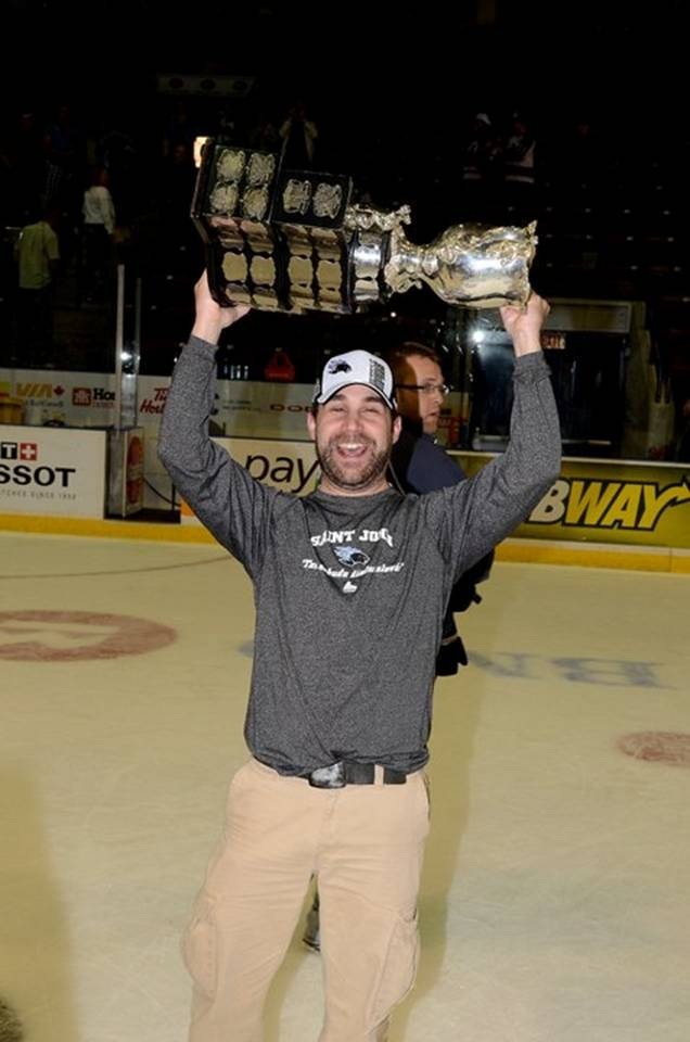 Jeff Kelly in a hockey rink holding a trophy above his head